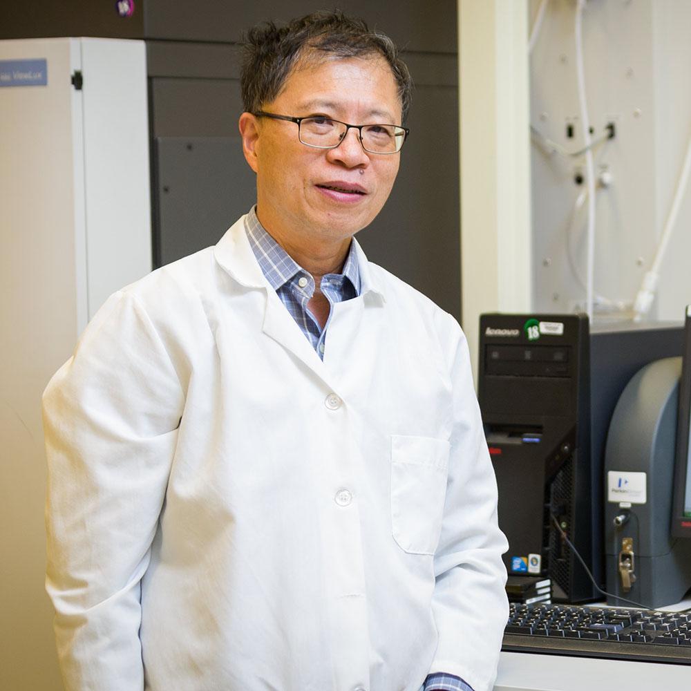 Dr. Wei Zheng standing next to a computer